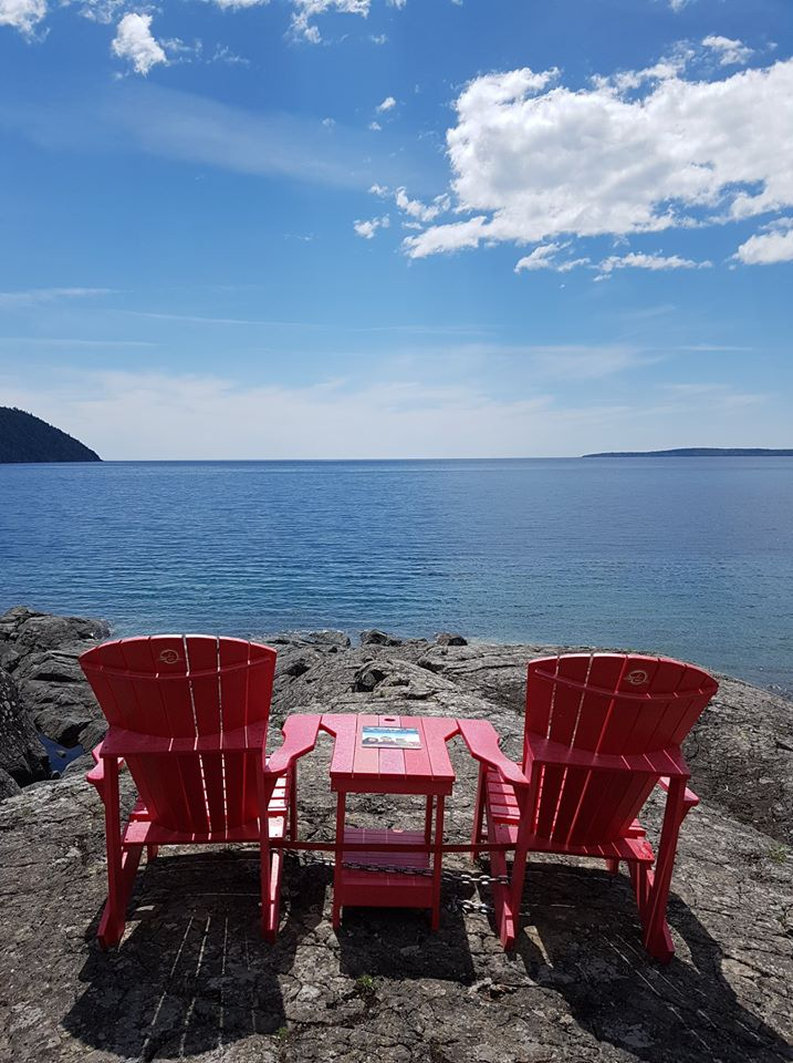 Red chairs sitting on rocks overlooking Lake Superior