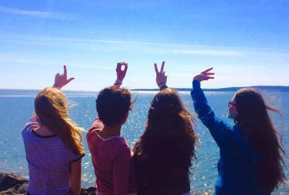 Young Women spelling out love with their hands at Schreiber Beach