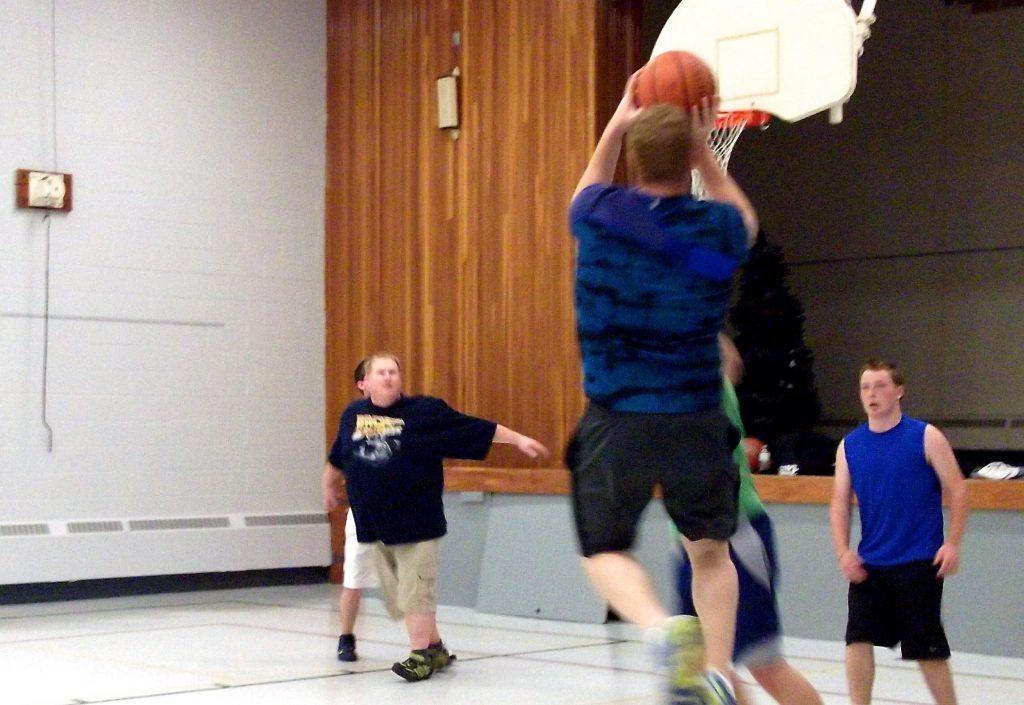 Man in shorts shooting a basket ball towards a basket ball net